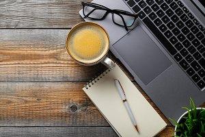 Desk with laptop, eyeglasses, notepa