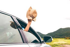Woman hand holding hat on the car