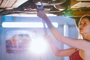Sexy mechanic girl repairs the car