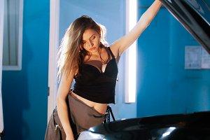Sexy mechanic girl opens up a car