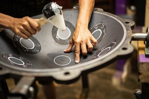 Hands constructing handpan