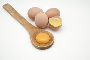 egg white and yolk on wooden spoon
