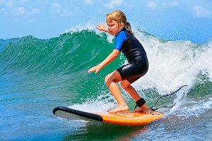 Young surfer rides on surfboard with