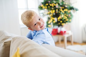 A small boy leaning on a sofa at