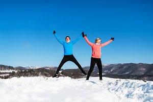 Happy senior couple runners jumping