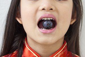 Little girl Eating Black grape