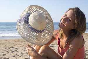 Happy girl show her hat on the beach