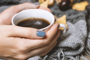 Cup of coffee in female hands.