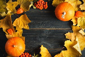Pumpkins with fall leaves over woode
