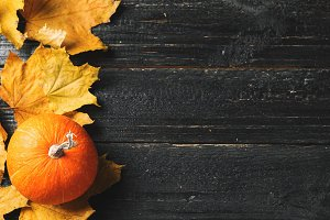 Autumn leaves and pumpkin over old w