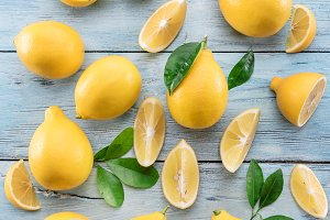 Ripe lemons and lemon leaves on blue