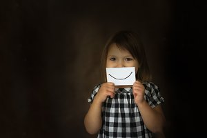 Funny kid girl with cardboard smile