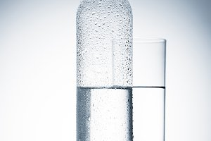 plastic bottle and glass of water on