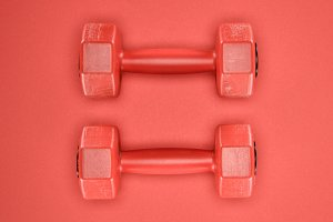Red shiny dumbbells isolated on red