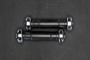 Black shiny dumbbells on black backg