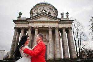 Wedding couple hugging against baroq