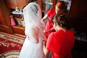 Helpful bridesmaids helping bride to