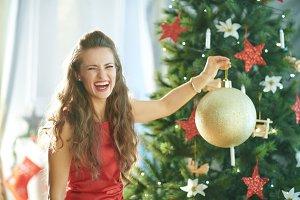 woman near Christmas tree showing bi