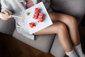 Young woman eating sushi in cosy
