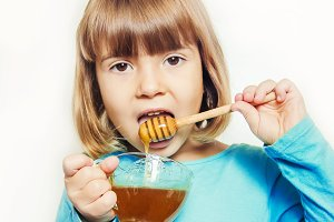 The child eats honey. Selective focu