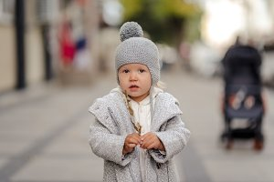 White-haired baby girl in a grey hat