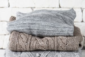 Stack of cozy woolen clothes on whit