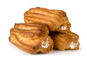 Three eclairs with cream on a white