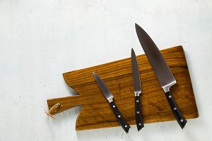 a set of knives on a wooden cutting