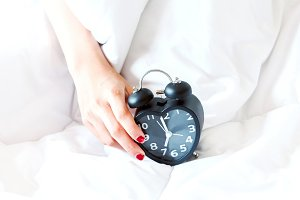 Woman holding alarmclock on the bed