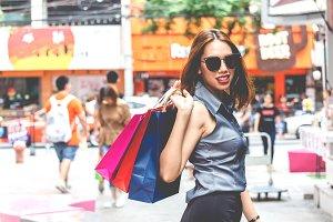 Woman holding shopping bag walking