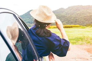 Woman relaxing out of window in car