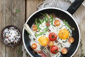 Pan of fried eggs, bacon tomatoes