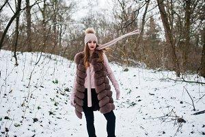 Stylish girl in fur coat and headwea
