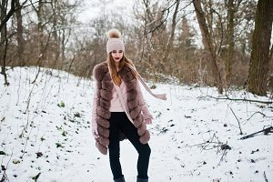 Stylish girl in fur coat and headwea