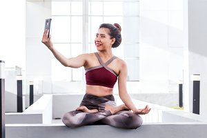 Woman practicing yoga and use tablet