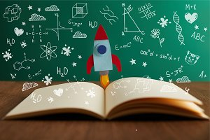 open book with colorful rocket on wo