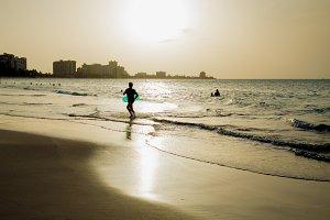Boy With Inner Tube Running on Beach