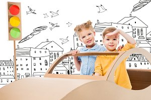 siblings playing with cardboard car