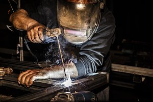 Welder in mask welds steel