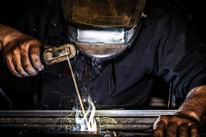 Man welding metal and sparks metal.