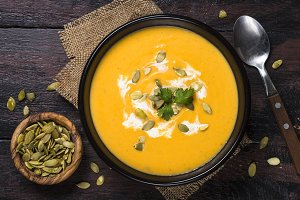 Pumpkin soup on dark wooden table to