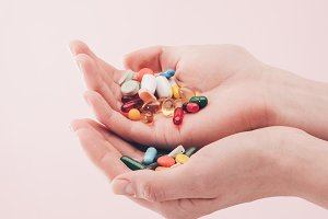 partial view of woman holding pills