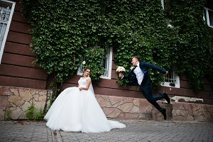 Elegant bride posing against the ivy