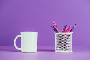 cup and pen holder on purple surface