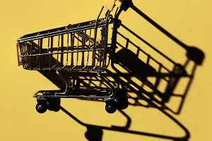 one shopping cart with shadow on yel
