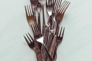 Old metal forks on white background