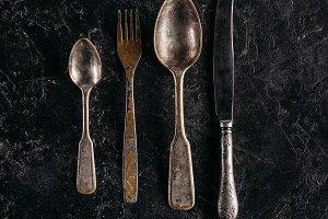 Old rusted silverware set on dark ma