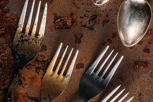 Vintage cutlery set on rusted backgr