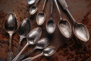 Old metal spoons on rusted backgroun