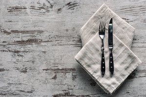 Metal fork with knife on napkin on w